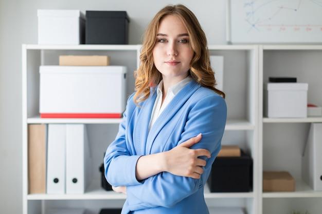 La bella ragazza sta vicino ad uno scaffale nell'ufficio.