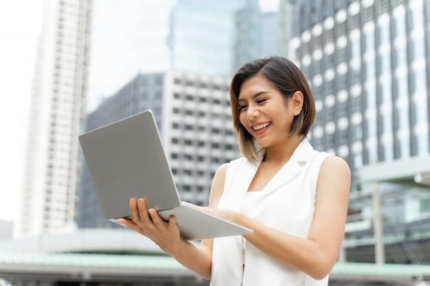 La bella ragazza sveglia che sorride in donna di affari copre facendo uso del computer portatile