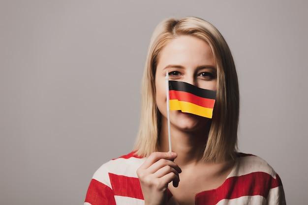 La bella ragazza tiene la bandiera tedesca