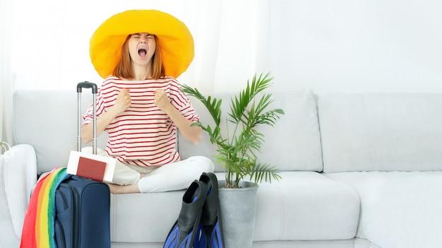 La bella ragazza turbata in un cappello giallo rimane a casa e pianifica un viaggio in vacanza. in attesa di viaggio.