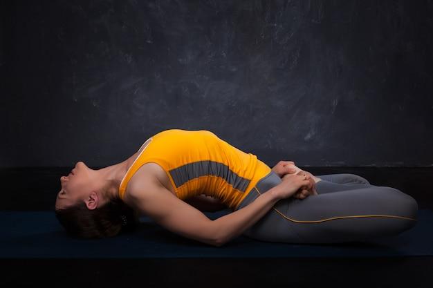 La bella ragazza yogi in forma sportiva pratica lo yoga asana matsyasana