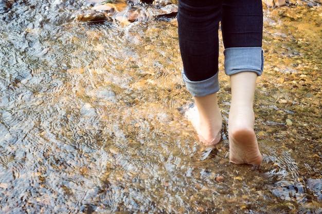 La bella signora che indossa jeans sta camminando sulle pietre nel fiume.