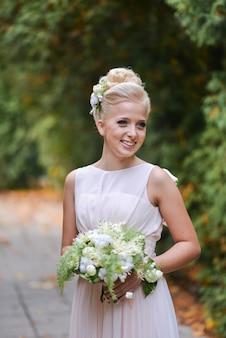 La bella sposa bionda elegante sta stando in un parco sulla strada con un mazzo insolito di autunno