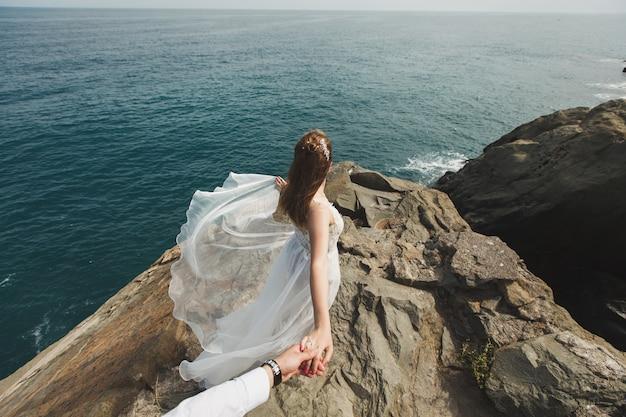 La bella sposa della giovane donna tiene la mano di un uomo dentro all'aperto