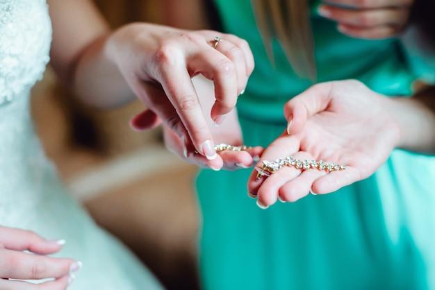 La bella sposa elegante sta indossando gli orecchini di mattina il suo giorno del weddig