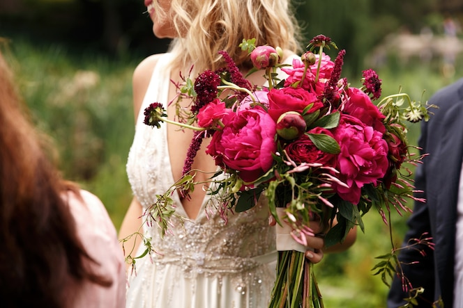 La bella sposa regge un ricco mazzo di peonie rosa scuro nel suo braccio