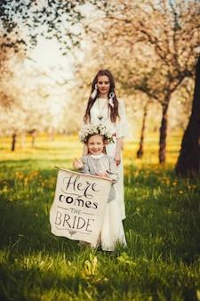 La bella sposa si leva in piedi vicino alla bambina