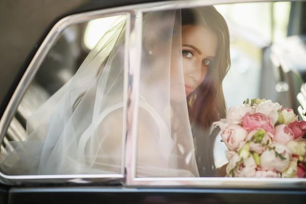 La bella sposa si siede con il mazzo di nozze in un'auto retro e si diverte
