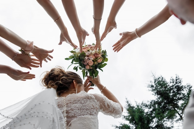 La bella sposa sta tenendo un mazzo variopinto di nozze