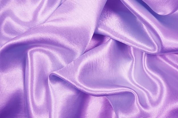 La bella struttura di lusso del panno del raso porpora può usare come fondo di nozze, tessuto