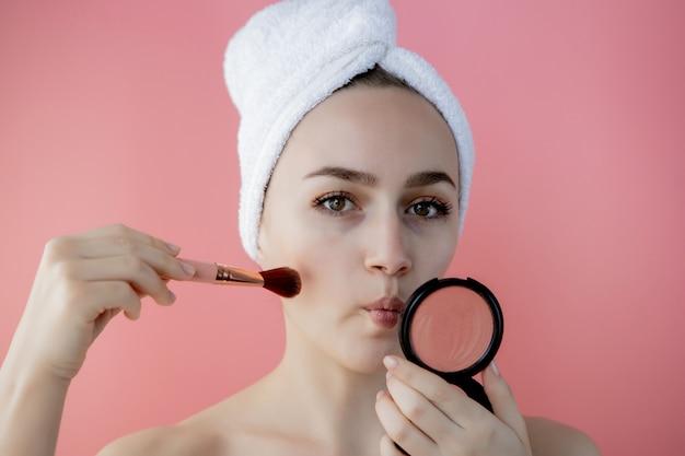 La bella tenuta della donna arrossisce la spazzola per applicare il fard sulle guance su fondo rosa