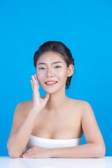 La bellezza delle donne con immagini perfette di salute della pelle toccando il suo viso e sorridendo come una spa per coccolarla. blu