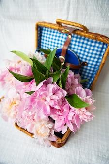 La bellezza di un bouquet di peonie rosa in un'autentica valigia marrone vintage.