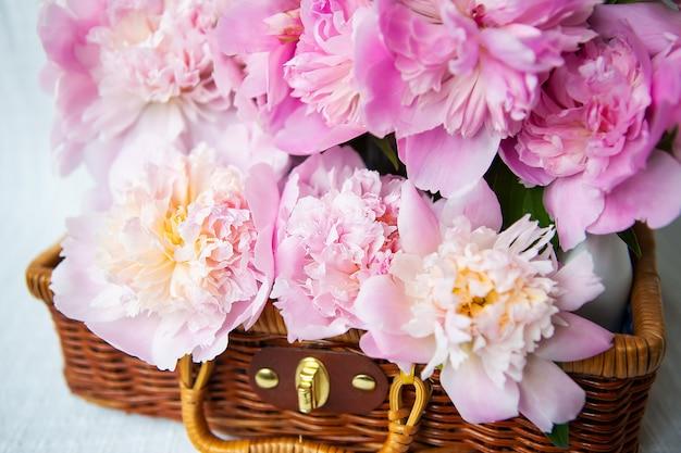 La bellezza di un bouquet di peonie rosa in una valigia marrone autentica vintage, primo piano.