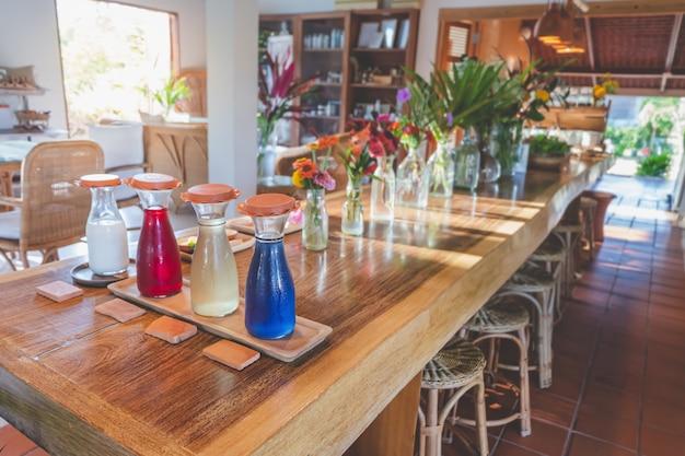 La bevanda e la frutta tradizionali della bevanda con il mazzo fioriscono e foglie sulla tavola di legno con la luce del sole
