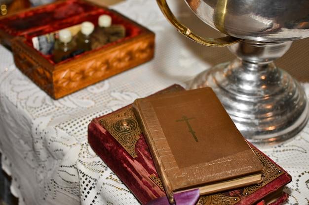 La bibbia giace sul tavolo con il calice nella chiesa prima del rito del battesimo
