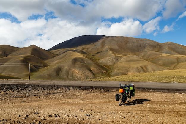 La bici del viaggiatore con le borse si trova accanto alla strada sullo sfondo di montagne, paesaggio, kirghizistan, bici da turismo