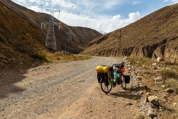 La bici del viaggiatore con le borse si trova sulla strada di montagna, fiume kokemeren, kirghizistan, bici turistica
