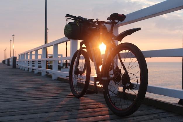 La bicicletta con le borse è sul molo sul mare, all'alba