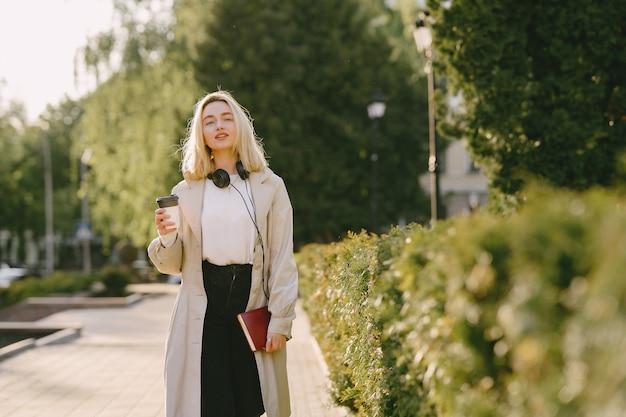 La bionda cammina nella città dell'estate con la tazza di caffè