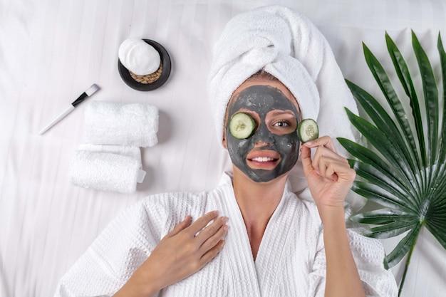 La bionda posa in un asciugamano sulla testa in posa con una maschera di argilla sul viso e un cetriolo su un occhio e l'altro in mano