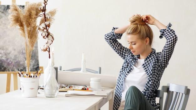 La bionda seduta al tavolo in officina raccoglie i capelli in una crocchia, in modo che non interferiscano con le note, disegnando con una matita su carta