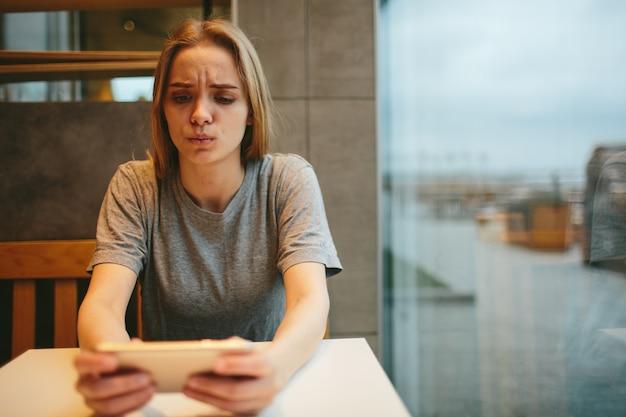 La bionda usa il telefono. ragazza e smartphone una donna è seduta in un bar con un cellulare