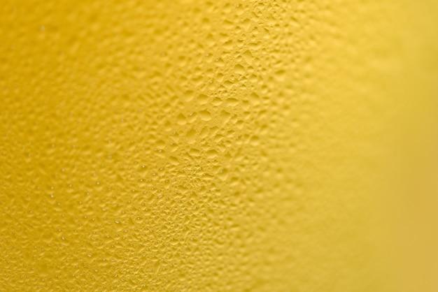 La birra bolle fine in su di birra della tazza con goccia di acqua su struttura