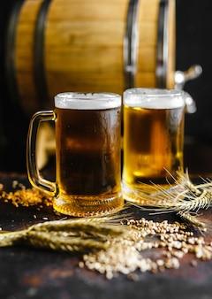 La birra e il grano aromatizzano su una vecchia tavola di legno