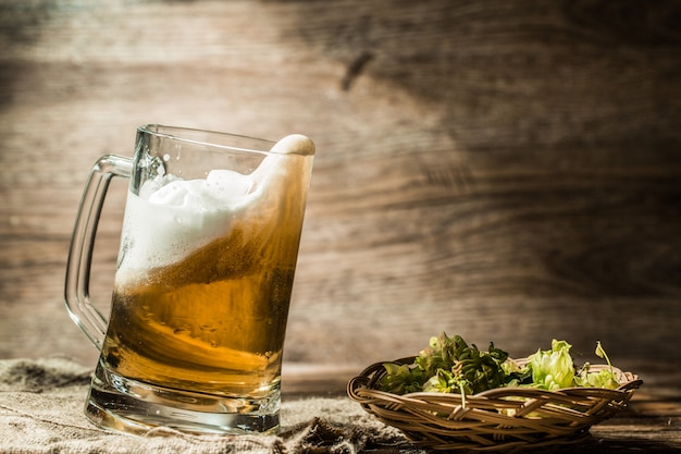 La birra si rovescia dal boccale con coperchio su fondo di legno vuoto