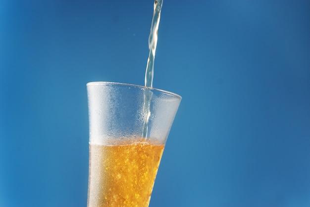 La birra viene versata su un bicchiere contro una superficie blu