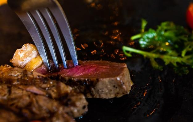 La bistecca del primo piano ha tagliato nelle fette servite sul piatto con il cucchiaio pieno delle spezie.