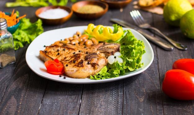 La bistecca di maiale che cucina casalinga con le spezie lascia la lattuga sul tagliere di legno