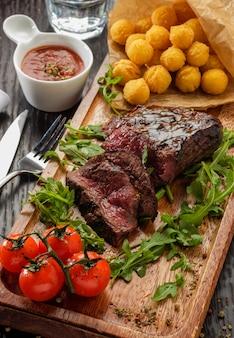 La bistecca di raccordo arrostita saporita succosa è servito con i pomodori e le palle del formaggio su un bordo di legno anziano.