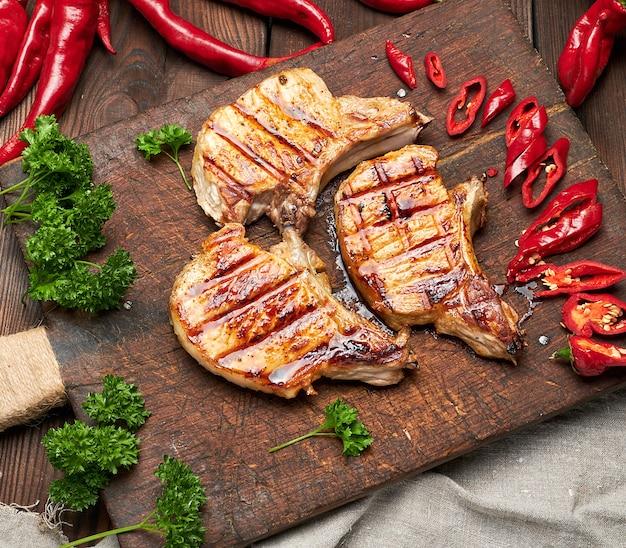 La bistecca fritta carne di maiale sulla costola si trova su un bordo di legno marrone d'annata, accanto ai peperoncini rossi freschi, vista superiore