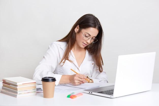 La blogger femmina indossa una camicia bianca, occhiali rotondi, scrive note nel blocco note, lavora al computer portatile, beve il caffè, è impegnata nello sviluppo di un webiste, utilizza una connessione interent wireless, isolata on white