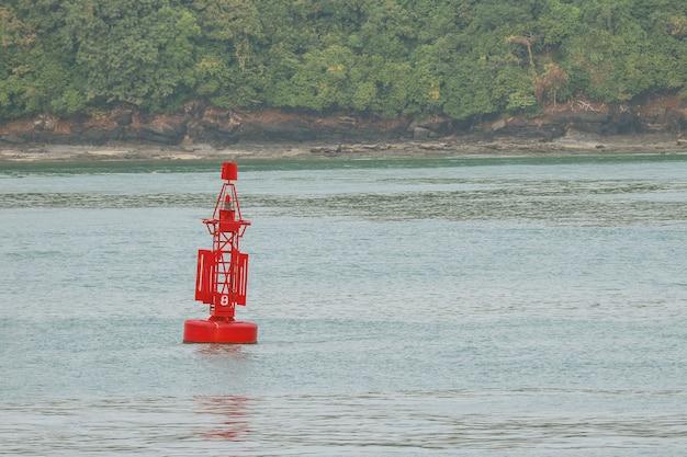 La boa rossa che galleggia sull'acqua di mare significa come luogo profondo.