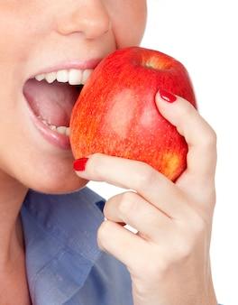 La bocca della ragazza graziosa che morde una mela isolata su un fondo bianco eccessivo