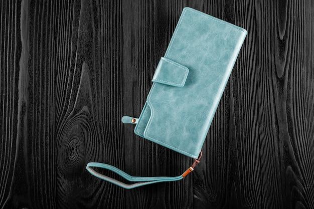 La borsa blu femminile isolata su di legno nero