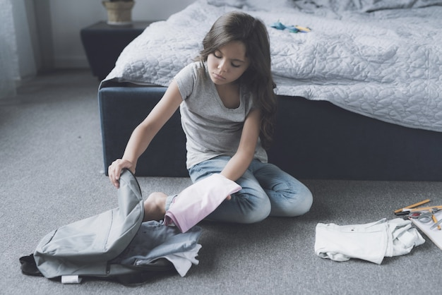 La borsa d'imballaggio sveglia della ragazza si siede sul pavimento in camera da letto