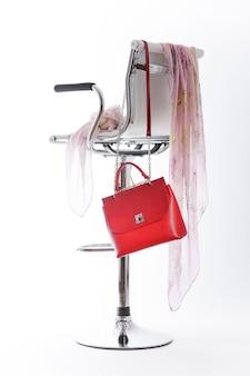 La borsa rossa è appesa alla sedia del visitatore.