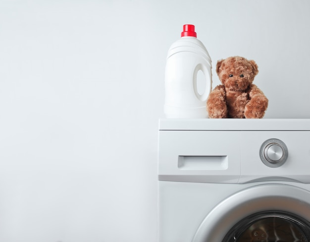 La bottiglia del gel di lavaggio liquido e l'orsacchiotto riguardano una lavatrice