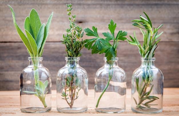 La bottiglia di olio essenziale con le erbe ha installato su vecchio fondo di legno.