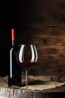 La bottiglia ed il vetro di vino rosso sul barilotto di legno hanno sparato con fondo di legno scuro