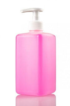 La bottiglia rosa di sapone liquido o il gel con una pompa su un bianco ha isolato il primo piano del fondo.