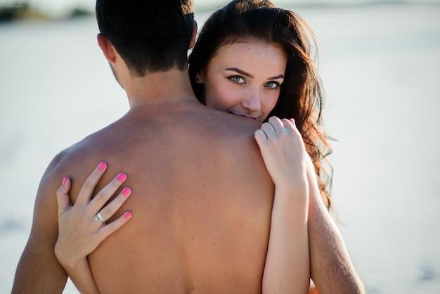 La brunetta strabiliante abbraccia l'uomo nudo e tiene le sue mani sulla sua parte posteriore