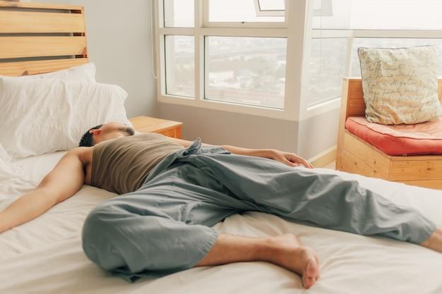 La bugia asiatica dell'uomo sul letto e si rilassa nel suo appartamento su calore domenica la primavera dell'estate.
