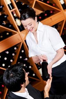 La cameriera offre una bottiglia di vino rosso