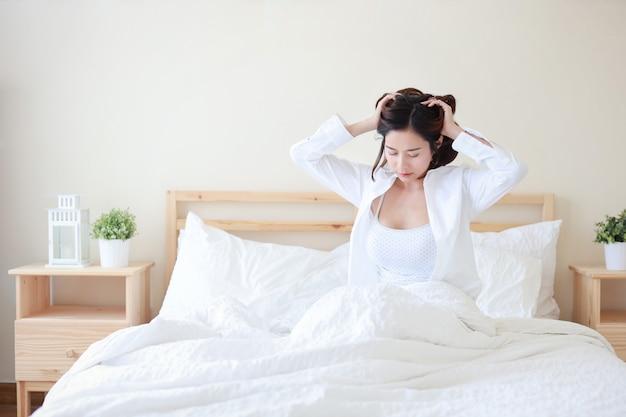 La camicia bianca d'uso della giovane donna asiatica allegra e sexy sveglia di mattina e sedendosi e allungando sul letto.