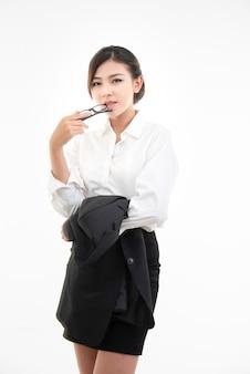La camicia bianca del vestito asiatico dalla donna di bellezza si spoglia l'isolato di vetro della tenuta della mano del vestito sulla parete bianca